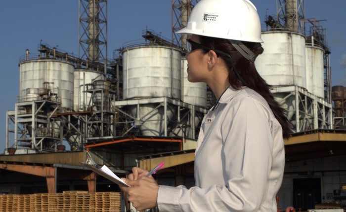 woman in hardhat holding a clipboard in front of our facility in Altamira, Mexico